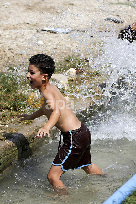 Palestinians cool off in the water of a natural spring known as Ein al-Sultan, near the West Bank city of Jericho on August 22, 2010. Photo by Eyad Jadallah