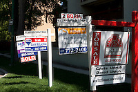 """For sale"" signs for Maximum realty, Re/Max, Zappia Group realty and Rischuk Park realty are seen next to each other in Winnipeg Thursday May 26, 2011."