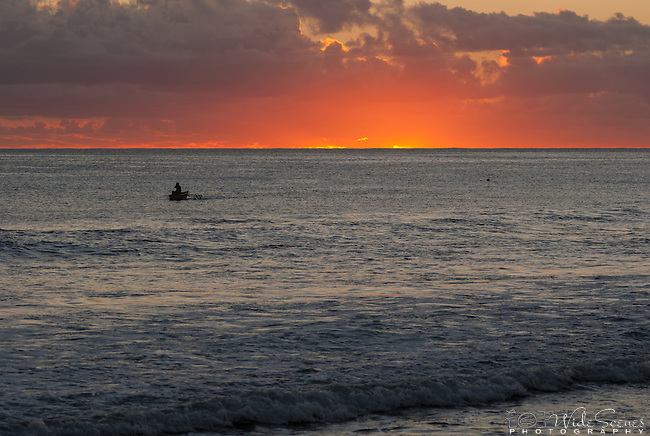 A local i-kiribati paddles during a magnificent sunset on the remote island of Kiritimati in Kiribati.
