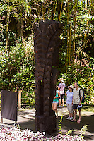 "Tourists read a sign next to a carved wooden tiki (or ki'i in Hawaiian, or statue) of the Hawaiian god ""KU"" at Hawai'i Tropical Botanical Garden, Onomea, Big Island of Hawaiʻi."