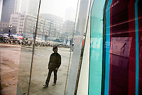 A man walks past the Deji Plaza shopping mall in the central Xinjeikou shopping area in Nanjing, Jiangsu, China.