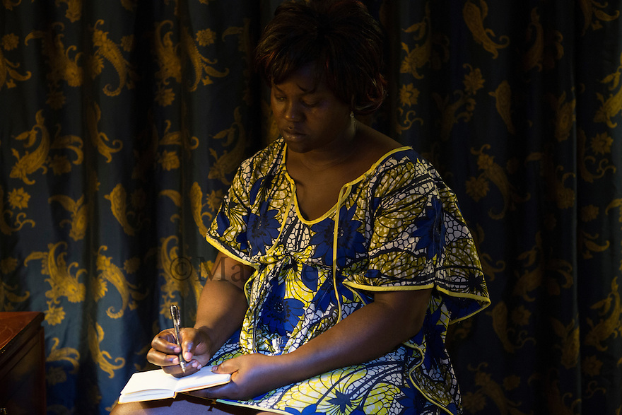 "Cameroon - Douala - Josianne Kokeke, 35, writing a letter to her 22 year old son Roger Morin Nankanp. Roger left two years ago with a friend, after a family dispute with his father. He moved to Central African Republic, with the intention of reaching Italy by boat. His mother had been in contact for the first year of his sejour in Central African Republic. It's been one year now since he hasn't communicated with him ""I am worried"" says Kokeke. ""Every evening I think about him. Where is he sleeping? Will he call me tomorrow?"""