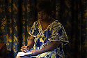 """Cameroon - Douala - Josianne Kokeke, 35, writing a letter to her 22 year old son Roger Morin Nankanp. Roger left two years ago with a friend, after a family dispute with his father. He moved to Central African Republic, with the intention of reaching Italy by boat. His mother had been in contact for the first year of his sejour in Central African Republic. It's been one year now since he hasn't communicated with him """"I am worried"""" says Kokeke. """"Every evening I think about him. Where is he sleeping? Will he call me tomorrow?"""""""