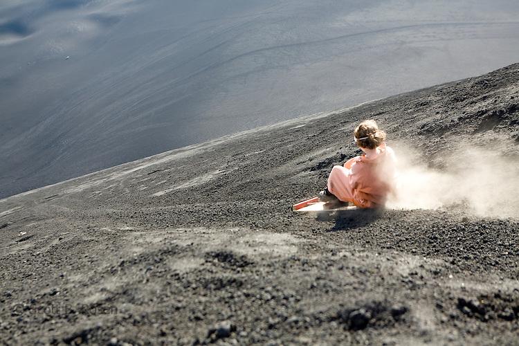 Woman boarding down the active Volcano Cerro Negro, Nicaragua