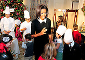 First lady Michelle Obama with military children in the State Dining Room of the White House during an event at the preview of the White House Christmas decorations in Washington, DC. The theme for the White House Christmas 2011 is Shine, Give, Share - celebrating the countless ways we can lift up those around us, put our best self forward in the spirit of the season, spend time with friends and family, celebrate the joy of giving to others, and share our blessings with all.  The theme translates to the holiday décor on several levels. There is the literal translation through the use of shiny elements – star motifs, quartz and metallics like copper, aluminum and mirrored paper. There is also a conceptual connection – we're inviting visitors to give their thanks to members of our military, and have once again invited guest artists to share their talents working with the White House. This year's décor also includes handmade decorations crafted from simple materials – paper, felt, and even recycled cans. These are projects that anyone can do at home using readily available materials that are inexpensive or free..Credit: Ron Sachs / CNP