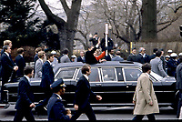 Washington, DC., USA, Janaury 20,1981<br /> President Ronald Reagan and First Lady Nancy Reagan wave to the crowds lining the inuagural parade route from the sun roof of their limousine. Their detail of Secret Service agents walk  along side the limousine as they leave the US Capitol grounds enroute to the White House. Credit: Mark Reinstein/MediaPunch