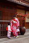 Japanese woman and her cute little daughter wearing red kimonos, yukatas, on the streets of Gion, Kyoto, Japan