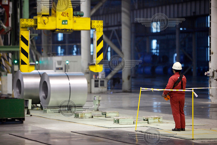 A worker operates a large lift to move newly made rolls of steel sheets at Ma Steel's new plant in Maanshan.