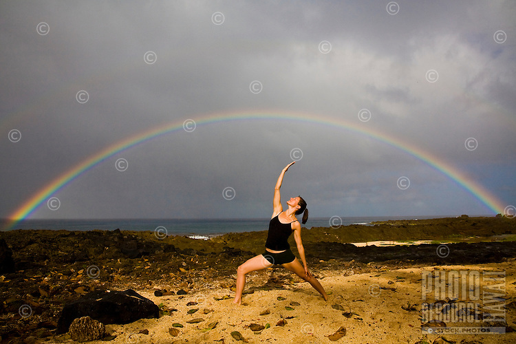 A young woman practicing a yoga pose under a double rainbow at Shark's Cove