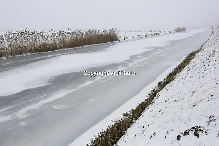 Foto: VidiPhoto..VALBURG - Een dichtgevroren Linge vrijdag bij Valburg, in een witte omgeving. Het is een van de weinige stromende riviertjes die dankzij de vorstperiode voorzien is van een flinke ijslaag. Net niet stevig genoeg om er op te kunnen schaatsen. De langste -geheel Nederlandse- rivier (108 km.) zou anders een van de mooiste toertochten van Nederland kunnen opleveren. De rivier loopt door twee provincies: Gelderland en Zuid-Holland..