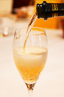 A champagne glass flute being filled with Gosset Grand Reserve champagne against a backdrop of a white table cloth, Restaurant Les Berceaux, Patrick Michelon, Epernay, Champagne, Marne, Ardennes, France