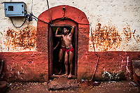 A young Kushti wrestlers looks out of the doorway during training at Gangavesh Talim on the 17th of September, 2017 in Kolhapur, India.  <br /> Photo Daniel Berehulak for Lumix
