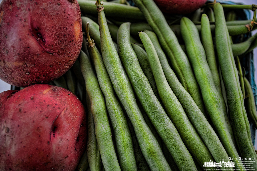 Fresh, crisp green beans and new red potatoes are paired in an offering at a famers market in July..