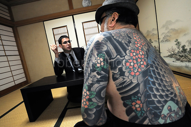 """Jake Adelstein, a former reporter at Japan's largest daily newspaper, Yomiuri Shimbun, and author of """"Tokyo Vice"""", speaks with his bodyguard, a former yakuza mobster who goes by the name """"Mochizuki,"""" at an undisclosed location in Japan on Aug. 29, 2008. In 2005 American Adelstein uncovered a scandal involving senior members of Japan's mafia, the yakuza, visiting a medical center in Los Angeles to undergo liver transplants, despite being bared from entry due to having criminal records or suspected affiliation with Japanese organized crime groups. Within days, however, Adelstein was visited by mob members and told to either """"erase the story or be erased."""" He took the former option and resigned from the Yomiuri, though a leak of his story at the time of this interview pushed Adelstein and his family into hiding..Photographer: Robert Gilhooly"""