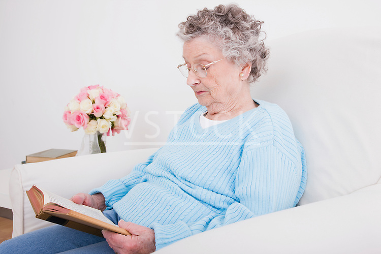 Senior woman sitting in armchair and reading book