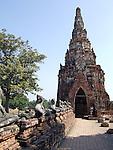 Row of headless Buddha and satellite prang of Wat Chai Wattanaram in Ayutthaya near Bangkok, Thailand.