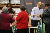 """United States President Barack Obama (2ND R) and first lady Michelle Obama help pack and distribute bags of food to needy children and seniors at the Capital Area Food Bank November 27, 2013 in Washington, DC. According to the White House, the first family was joined by family and friends and members of The Mission Continues, """"an organization of post-9/11 veterans who are awarded community service fellowships."""" <br /> Credit: Chip Somodevilla / Pool via CNP"""