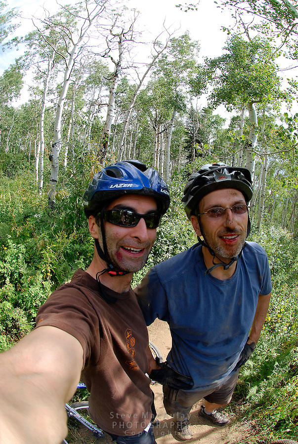 Self portrait of two male mountain bikers who crashed and have bloody faces, mountain biking on the trails at Steamboat Springs Resort, Steamboat,  Colorado.