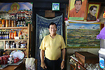 Owner at his restaurant, cafe, shop. With Buddhist and posters of the King. Nearby Tronsa Dzong, town centre, Bhutan..Bhutan the country that prides itself on the development of 'Gross National Happiness' rather than GNP. This attitude pervades education, government, proclamations by royalty and politicians alike, and in the daily life of Bhutanese people. Strong adherence and respect for a royal family and Buddhism, mean the people generally follow what they are told and taught. There are of course contradictions between the modern and tradional world more often seen in urban rather than rural contexts. Phallic images of huge penises adorn the traditional homes, surrounded by animal spirits; Gross National Penis. Slow development, and fending off the modern world, television only introduced ten years ago, the lack of intrusive tourism, as tourists need to pay a daily minimum entry of $250, ecotourism for the rich, leaves a relatively unworldly populace, but with very high literacy, good health service and payments to peasants to not kill wild animals, or misuse forest, enables sustainable development and protects the country's natural heritage. Whilst various hydro-electric schemes, cash crops including apples, pull in import revenue, and Bhutan is helped with aid from the international community. Its population is only a meagre 700,000. Indian and Nepalese workers carry out the menial road and construction work.