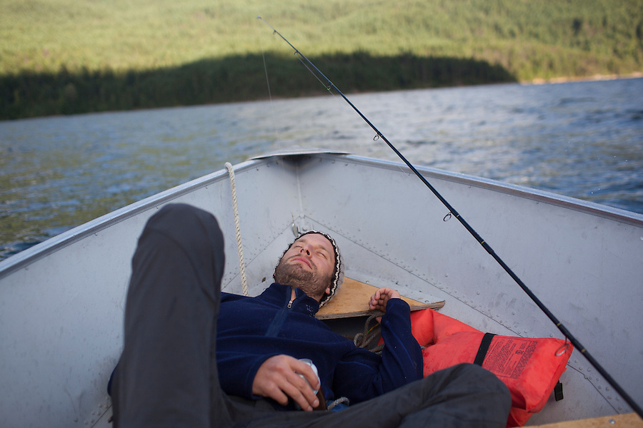 A man sleeps in the bow of a motorboat on Ross Lake, WA, USA