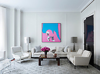 In the living room, the leather armchair is by Carlo di Carli and the rug is by Beauvais Carpets; the walls are painted in Benjamin Moore's Classic Gray. The bold, pink and blue artwork brings a bright spot of colour to the otherwise neutral room.