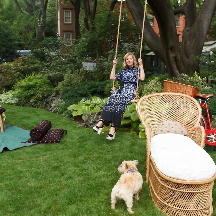 "Fashion designer Lela Rose plays on swing during Lela Rose Resort 2018 ""Garden Party"" collection presentation in Jefferson Market Garden on June 7 2017, during Resort Fashion Week in New York City."