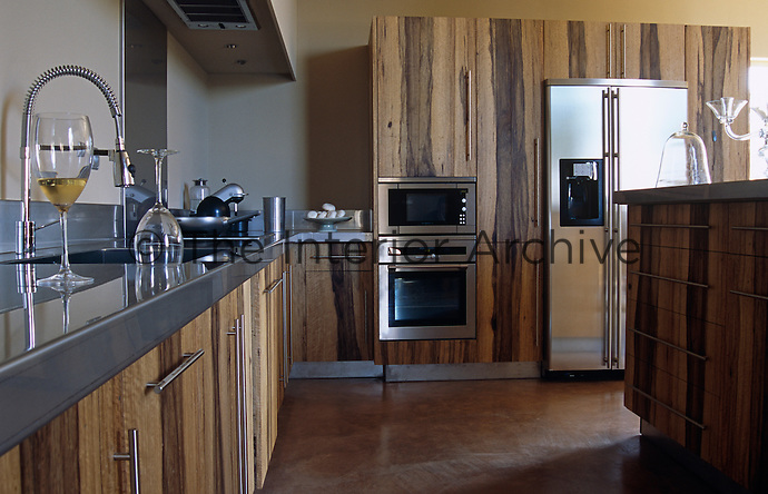 This contemporary kitchen features cabinets with distinctive wood veneer doors and stainless steel appliances and work surfaces
