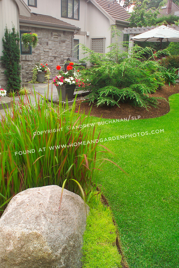Detail of a large decorative rock and Japanese Bloodgrass, with the lower-level dining and entertaining patio behind and below grade in this small backyard suburban garden east of Seattle. Design by Sander Groves landscapes, Inc.