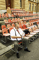 Switzerland. Canton of Neuchâtel. Neuchâtel. Grape Harvest Festival. University building. A fat old man seats alone on a red plastic chair before the start of the corso parade. © 2006 Didier Ruef