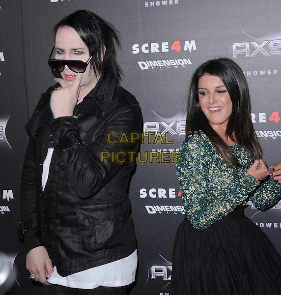 MARILYN MANSON (Brian Hugh Warner) & SHENAE GRIMES .at the Weinstein World Premiere of 'Scream 4' held at The Grauman's Chinese Theatre in Hollywood, California, USa, April 11th 2011..half length pose posing back to back green print top skirt jacket  hand funny  black sunglasses aviators .CAP/RKE/DVS.©DVS/RockinExposures/Capital Pictures.