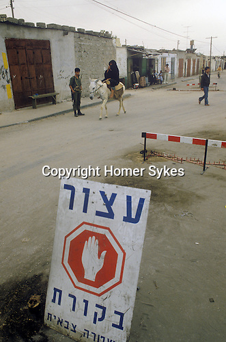 Israel 1982. Rafah border crossing. Bedouin woman on donkey. <br /> <br /> The Hebrew stop sign reads: Military police checkpoint ahead.