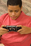 15 year old teenage boy at home playing handheld eletronic game vertical Hispanic Puerto Rican
