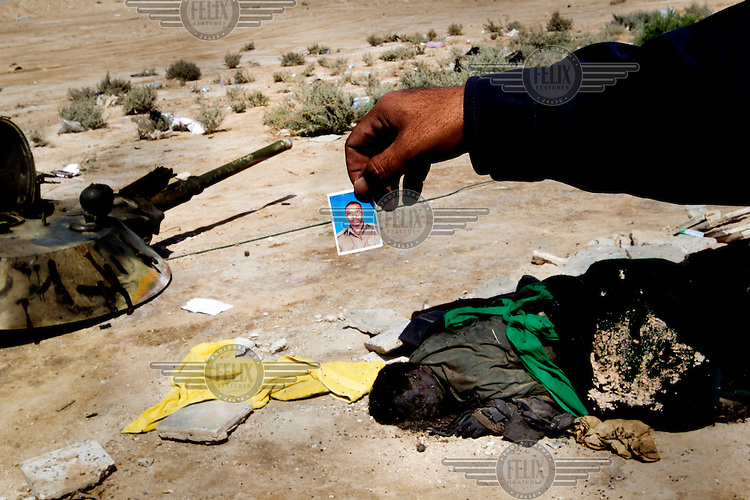 A man holding up a picture taken from a dead pro-Gadaffi fighter lying on the ground next to destroyed military hardware. On 17 February 2011, an uprising against the 41 year rule of Col Muammar Gadaffi started in eastern Libya..