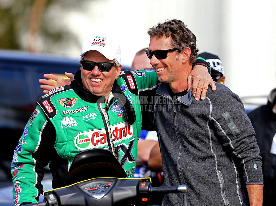 Feb 7, 2014; Pomona, CA, USA; NHRA funny car driver John Force (left) greets former driver Whit Bazemore during qualifying for the Winternationals at Auto Club Raceway at Pomona. Mandatory Credit: Mark J. Rebilas-