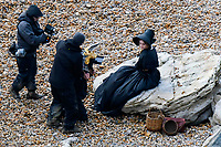BNPS.co.uk (01202 558833)<br /> Pic: Graham Hunt/BNPS<br /> <br /> Saoirse Ronan filming a scene on the Beach at Eype near Bridport in Dorset yesterday for the new film Ammonite about the life of fossil hunter Mary Anning.<br /> <br /> Saoire Ronan being filmed sitting on a rock.
