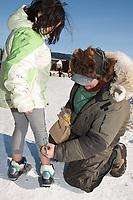 Ray Redington Jr. autographs a young girl's pants at the village of Koyuk in Arctic Alaska during the 2010 Iditarod