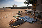 Bodies lie near the drainage pipe where Col. Muammar Gaddafi was found, one day after his capture and death in Sirte, Libya, Oct. 21, 2011. Gaddafi's convoy was hit by a NATO airstrike about a half hour after they left District 2 where he was hiding in Sirte. Two revolutionary brigades battled members of the convoy before finding Gaddafi hiding in the pipe. Some of the people appeared to have been executed and several showed signs of injury.
