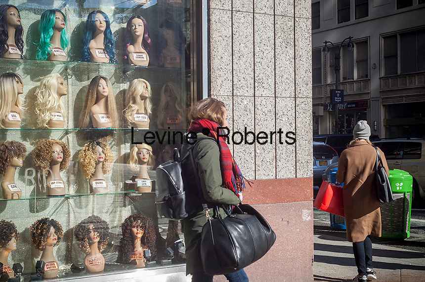 A woman walks past a wig store in Midtown Manhattan in New York on Sunday, January 15, 2017. (© Richard B. Levine)