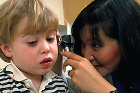 A health care worker examines the ears of a young boy in a medical office.