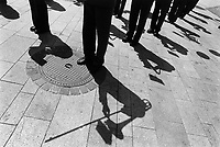 Switzerland. Geneva. Town Center. Shadows on the street of fanfare's musicians playing on Music Day. A slide trombone is a musical wind instrument consisting of a cylindrical metal tube expanding into a bell and bent twice in a U shape, usually equipped with a slide (slide trombone).Trumpets are brass instruments. Manhole drain cover on the road. A fanfare is a short musical flourish that is typically played by various brass instruments, often accompanied by percussion. A marching band is a group in which instrumental musicians perform while marching often for entertainment. The Fête de la Musique, also known in English as Music Day, Make Music Day or World Music Day, is an annual music celebration that takes place on 21 June ( but usually during the previous or following weekend). On Music Day the citizens of a city or country are allowed and urged to play music outside in their neighborhoods or in public spaces and parks. Free concerts are also organized, where musicians play for fun and not for payment. 22.06.1993 © 1993 Didier Ruef