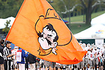 13 October 2012: The Oklahoma State players take the field behind a large banner of a Cowboy. The Oklahoma State University Cowboys played the University of Kansas Jayhawks at Memorial Stadium in Lawrence, Kansas in a 2012 NCAA Division I Football game.