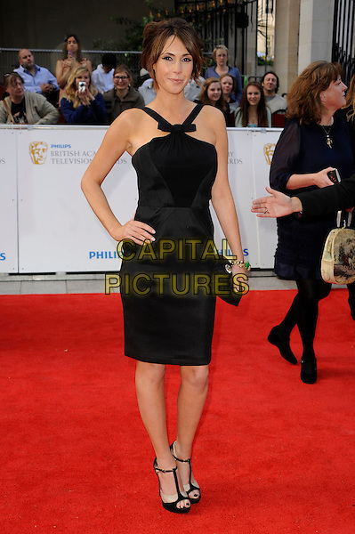 ALEX JONES .Attending the Philips British Academy Television Awards, Grosvenor house Hotel, Park Lane, London, England, UK, May 22nd 2011..arrivals TV Baftas Bafta full length black dress bow sleeveless straps  t-bar shoes sandals clutch bag peep toe hand on hip .CAP/WIZ.© Wizard/Capital Pictures.