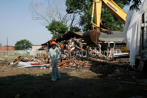 Saint Bernard's Parish, Louisiana.May 31, 2006..The home of Kim and Nanette Hery is demolished after suffering major damage from flooding. Workers are made to wear special clothing, gloves and breathing masks as the home contains asepses.