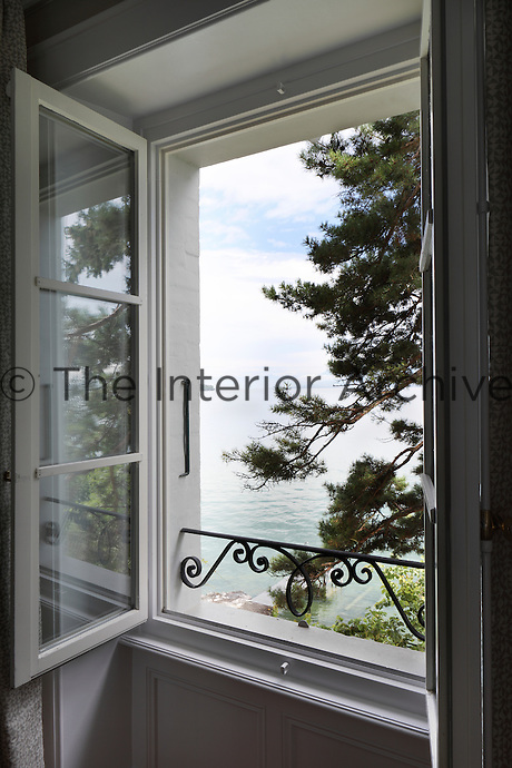 A romantic, tree framed view across the serene waters of Lake Geneva from one of the upstairs windows
