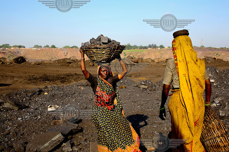 Women scavenging coal carry baskets full of large blocks of the rock that they've taken illegally from an open-cast mine near the village of Bokapahari where a community of coal scavengers live and work. /Felix Features
