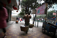 CHINA. Sichuan Province. Chongqing. A man carrying goods. Chongqing is a city of over 3,000,000 people, famed for being the capital of China between 1938 and 1946 during World War II. It is situated on the banks of the Yangtze river, China's longest river and the third longest in the world. Originating in Tibet, the river flows for 3,964 miles (6,380km) through central China into the East China Sea at Shanghai.  2008.