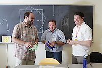 New York, NY, USA - June 26, 2011: Peter Engel (center), Origami designer, teaching his students Andrew Chizhik (left) and Paul Frasco (right) a complex model of the sun.