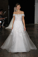 """Model walks runway in a """"Whisper"""" bridal gown from the Rivini by Rita Vinieris Fall 2017 collection on October 7th, 2016 during New York Bridal Fashion Week."""