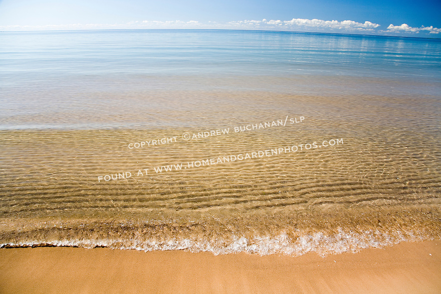 Ripples in the underwater sand as a small wave breaks along the shoreline of Lake Huron, in the eastern Upper Peninsula of Michigan with a blue summer sky and puffy white clouds above the distant curving horizon.