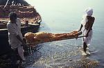 INDIA Varanasi, cremation of dead body at Manikarnika ghat at river Ganga , it is part of ritual moksha, hindu belief to come into heaven and get salvation from cycle of rebirth here / INDIEN Benares Varanasi Kashi , die Doms, unberuehrbare Kaste der Bestatter verbrennen die Toten auf Scheiterhaufen aus Holz am Manikarnika Ghat, die Leichen werden hier vorher in den heiligen Fluss Ganges getaucht , Hindus glauben an Moksha, wer in Benares stirbt oder verbrannt wird, entgeht dem Kreislauf der ewigen Wiedergeburten und kommt in den Himmel